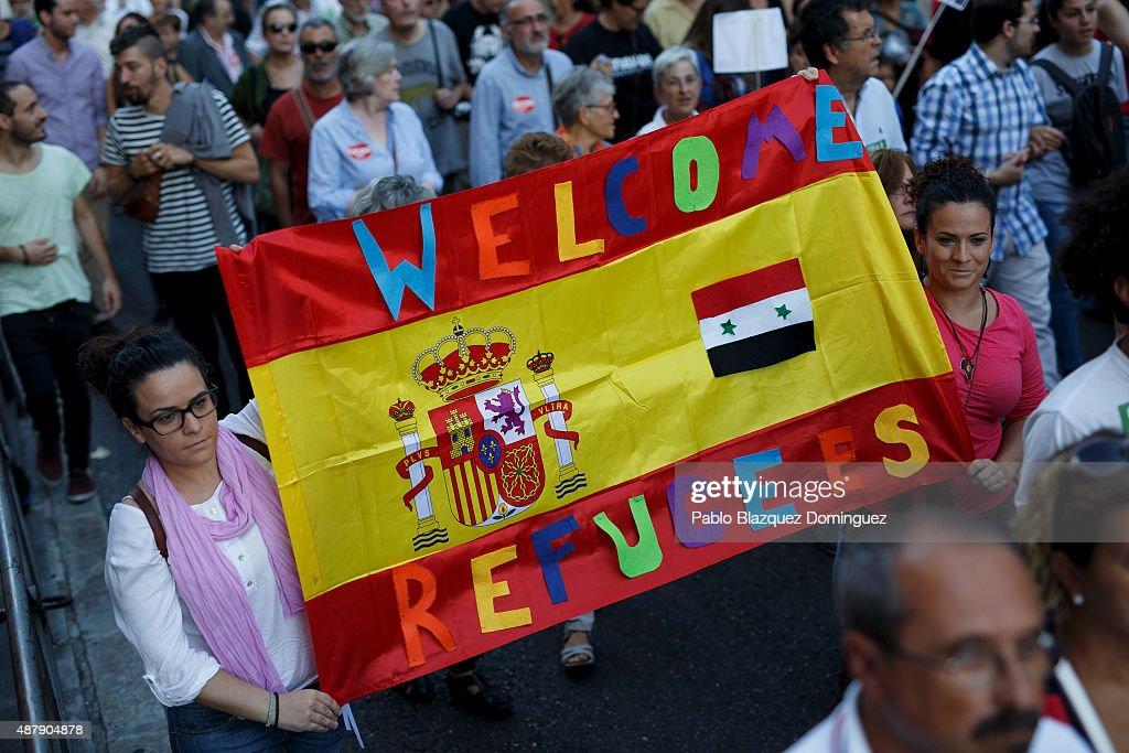 Protesters hold a Spanish flag reading 'Welcome refugees!' during a demonstration to show solidarity and support for refugees on September 12, 2015 in Madrid, Spain. Several cities across Spain have called for demonstrations under the slogan 'Welcome refugees. For a more responsible European policy'. Europe is facing the region's largest crisis of migrants and refugees since World War II. Spain would have to take nearly 15,000 refugees under a new European Union plan to relocate 120,000 refugees. Many Spanish cities and citizens took the lead on offering their support to refugees.