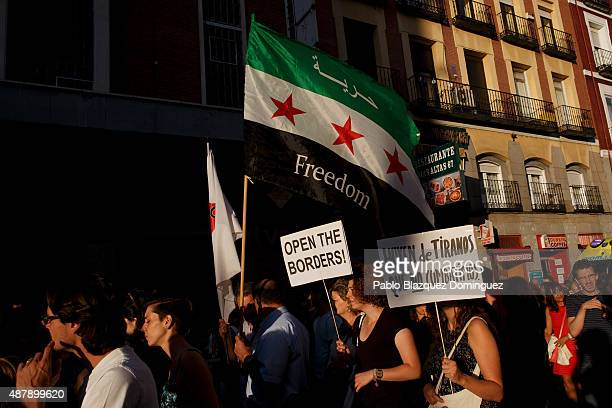 Protesters hold a Syrian Independent flag and placards reading 'Open the borders' and 'They are fleeing from tyrants that we don't fight' during a...