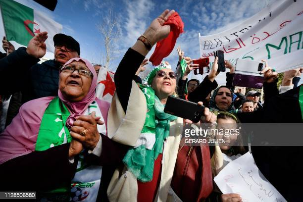 TOPSHOT Protesters hold Algerian national flags during a sitin against the Algerian president's bid for a fifth term in office on March 3 2019 in...