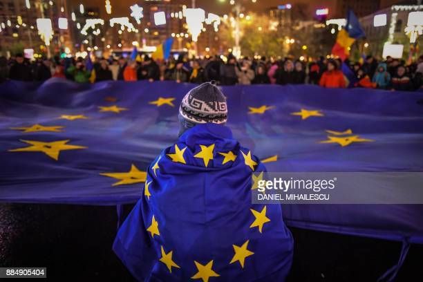 Protesters hold an EU flag during an anti-government and corruption protest, at the Victoria square in front of the Romanian Government headquarters,...