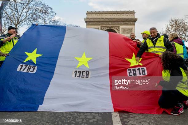 Protesters hold an oversized french flag during the 'Yellow vests' demonstration on the Champs Elysees on December 8 2018 in Paris France The 'Yellow...