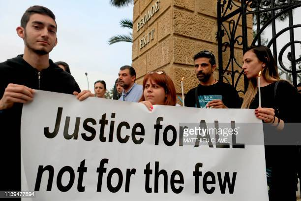 Protesters hold banners and candles as they demonstrate in support of the victims of a suspected serial killer in front of the presidential palace in...