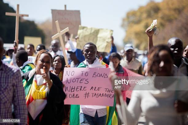 TOPSHOT Protesters hold banners and crosses during a march against the introduction of new bond notes and youth unemployement on August 2016 in...