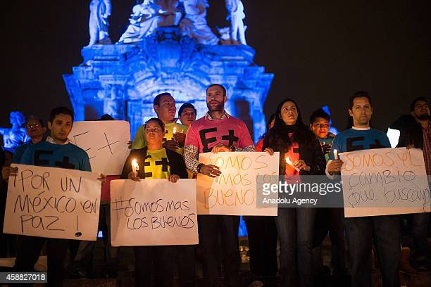 Protesters hold banners and light candles at the Angel of Independence in Mexico City Mexico on October 11 2014 during a protest demanding the...