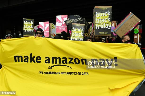 Protesters hold banners and placards during a demonstration to ask the online retailer Amazon to pay its employees fairly on November 24 2017 on the...