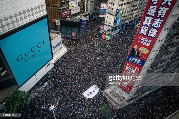 Protesters hold banners and shout slogans as they march on a street on June 16 2019 in Hong Kong China Large numbers of protesters rallied on Sunday...