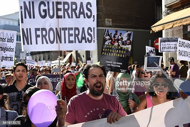 Protesters hold banners and shout slogans during a protest in Madrid in support of refugees and migrants An estimated 100 people gathered at 'Retiro'...