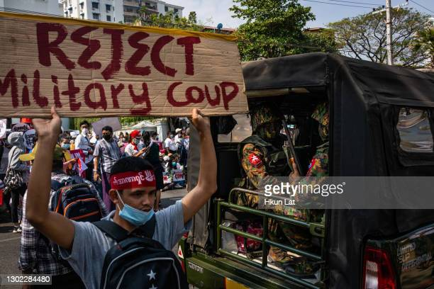 Protesters hold banners and shout slogans while marching past Myanmar military soldiers who arrived to guard the Central Bank overnight on February...