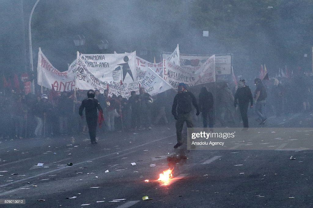 Protesters hold banners and throw molotov bombs during a protest against government's austerity policy, in front of parliament building in Athens, Greece on May 8, 2016. Clashes break out ahead of reforms voting.