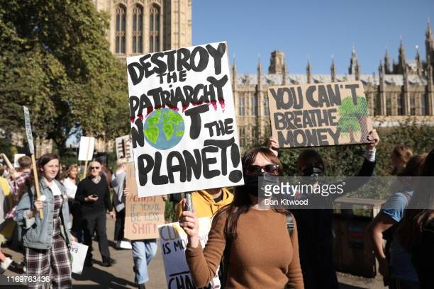 Protesters hold banners as they attend the Global Climate Strike on September 20 2019 in London England Millions of people are taking to the streets...