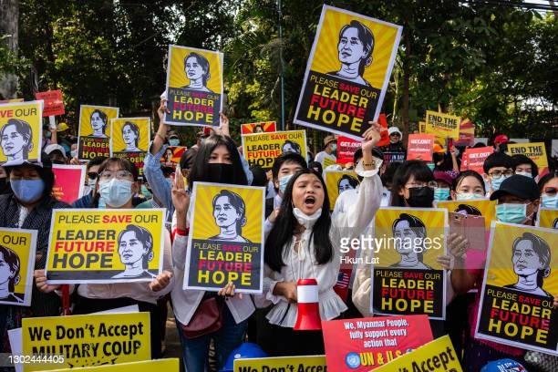 Protesters hold banners as they gather outside the U.S. Embassy for a protest against the military coup on February 16, 2021 in Yangon, Myanmar. The...