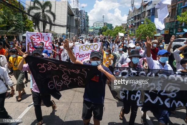 Protesters hold banners as they make the three-finger salute during a demonstration against the military coup in Yangon on May 12, 2021.