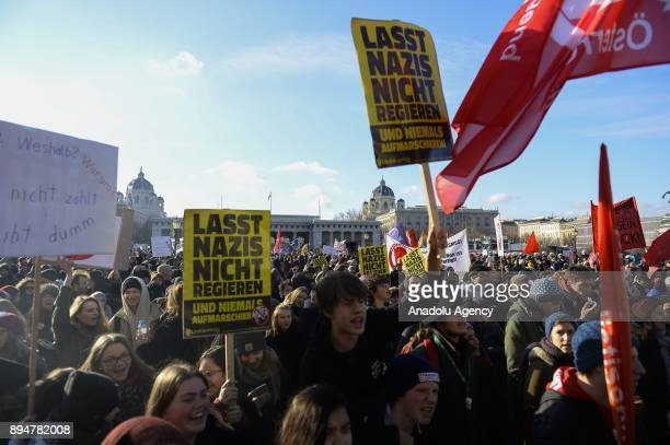 Protesters hold banners during a demonstration against the new Austrian government during the swearingin day at Heldenplatz Vienna Austria on...