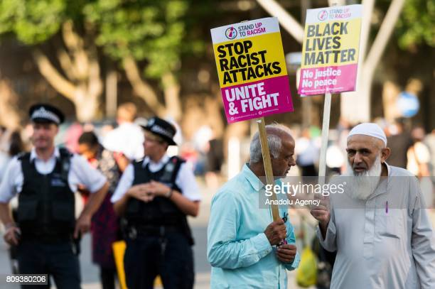 Protesters hold banners reading Black Lives Matter No Justice No Peace Stop Racist Attacks Unite And Fight at a vigil for Resham Khan and Janeel...
