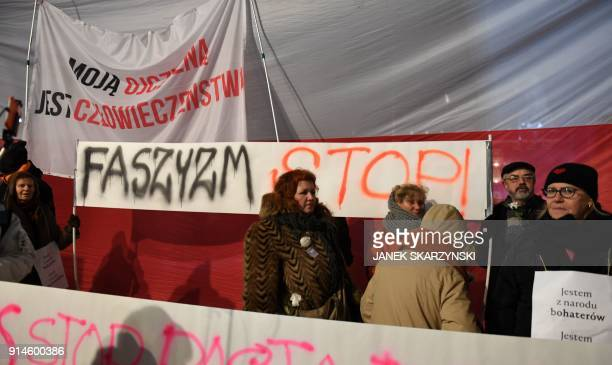 Protesters hold banners reading 'stop facism' and 'My fatherland is humanity' during a demonstration against a controversial new Polish bill...