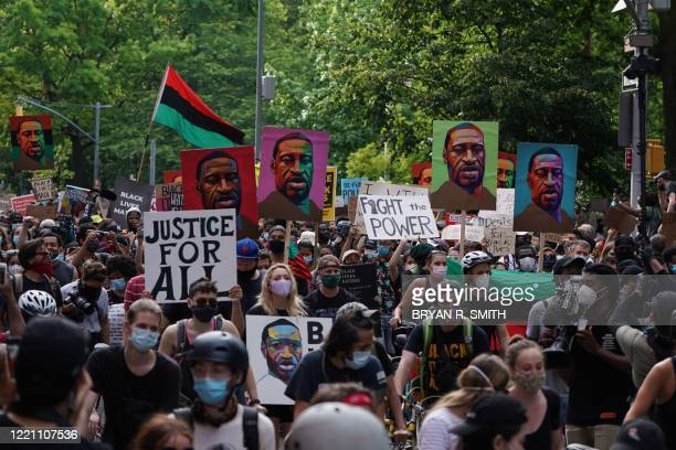 """Protesters hold """"Black Lives Matter"""" signs and pictures of George Floyd as they march through Greenwich Village in a demonstration over the death of..."""
