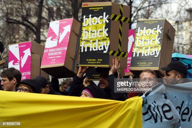 Protesters hold boxes with slogans during a demonstration to ask the online retailer Amazon to pay its employees fairly on November 24 2017 on the...