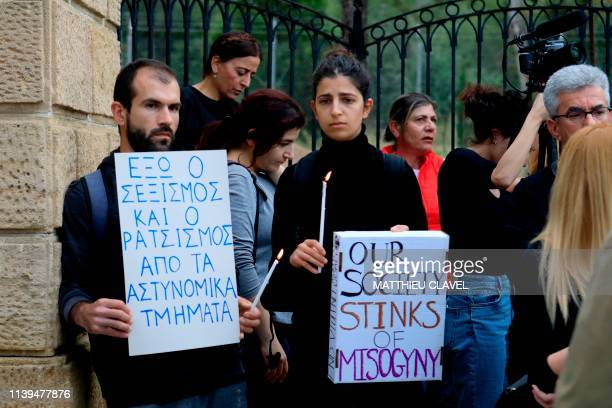 Protesters hold candles as they demonstrate in support of the victims of a suspected serial killer in front of the presidential palace in Nicosia on...
