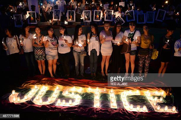 Protesters hold candles during a vigil inside the campus of the state university in Manila on October 24 to coincide with the burial of murdered...