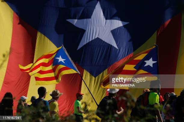 """Protesters hold Catalan pro-independence """"Estelada"""" flag as they walk on the AP-7 highway near Girona, on October 16 a day after police arrested 51..."""