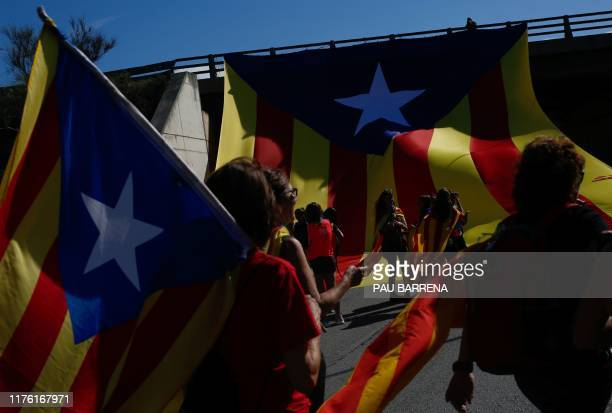 Protesters hold Catalan proindependence Estelada flags as they march on the Nacional 2 road in Sils near Girona on October 16 a day after police...