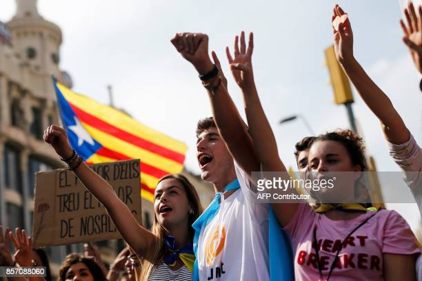 Protesters hold Catalan pro-independence 'Estelada' flags during a general strike in Catalonia called by Catalan unions in Barcelona, on October 3,...