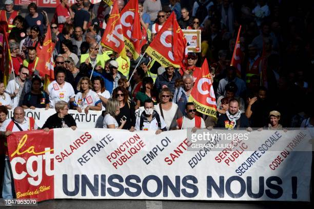 Protesters hold CGT union flags as they demonstrate on October 9 2018 in Marseille southern France during a day of interprofessional mobilisation...