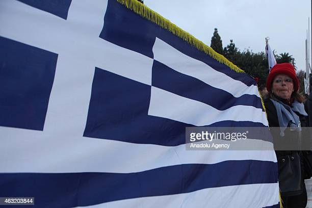Protesters hold flag of Greece as they gather outside the Greek parliament building as they take part in a solidarity rally with the Greek government...