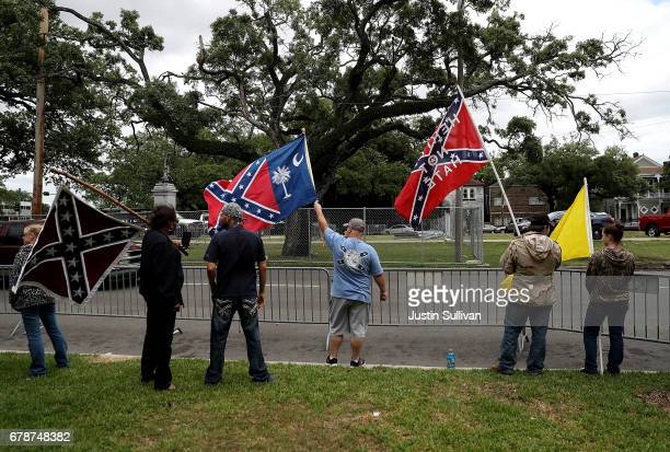 Protesters hold flags across the street from the Jefferson Davis monument on May 4 2017 in New Orleans Loiusiana The Louisiana House committee on...