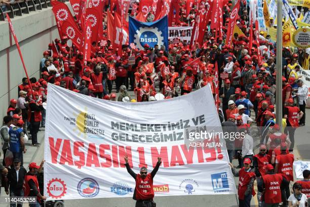 Protesters hold flags and banners as they demonstrate to mark May Day on May 1 in Ankara