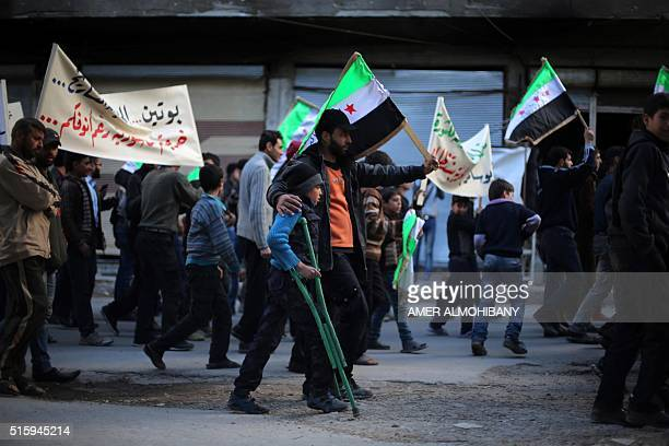 Protesters hold flags and placards during an antiregime demonstration in the rebelheld town of Saqba on the outskirts of the Syrian capital Damascus...