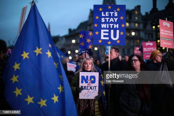 Protesters hold flags as they demonstrate on the day that MPs vote on Theresa May's Brexit deal in Parliament Square on January 15 2019 in London...