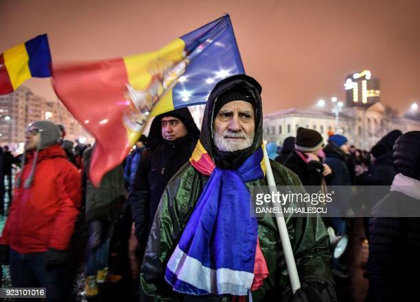 Protesters hold flags during a demonstration against corruption and the Justice minister on February 22, 2018 outside the Romanian government...