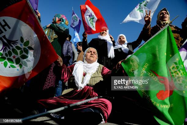 Protesters hold flags of the Peoples' Democratic Party during a rally in the Kurdishmajority city of Diyarbakir southeastern Turkey on January 19 in...