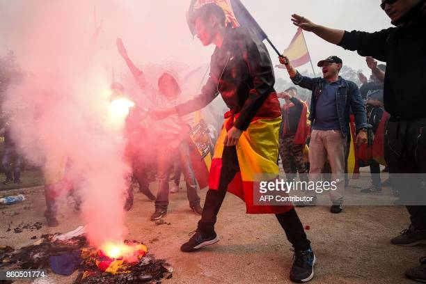 Protesters hold flares and burn a 'Estelada' Catalan proindependence flag during an ultraright wing antiseparatist demonstration for the unity of...
