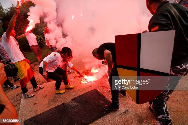 Protesters hold flares and burn 'Esteladas' Catalan proindependence flags during an ultraright wing antiseparatist demonstration for the unity of...