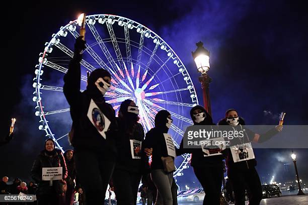 TOPSHOT Protesters hold flares beside the ferris wheel on the Place de la Concorde in Paris on November 24 during a demonstration by police over...
