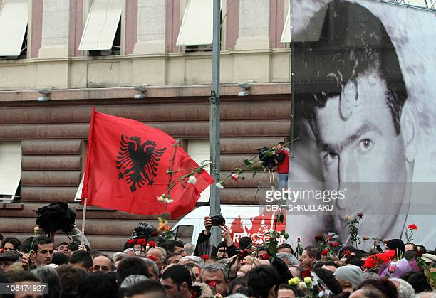 Protesters hold flowers in front of a giant portrait of Hekuran Deda one of the victims of last weeks deadly riots outside the Albanian Prime...