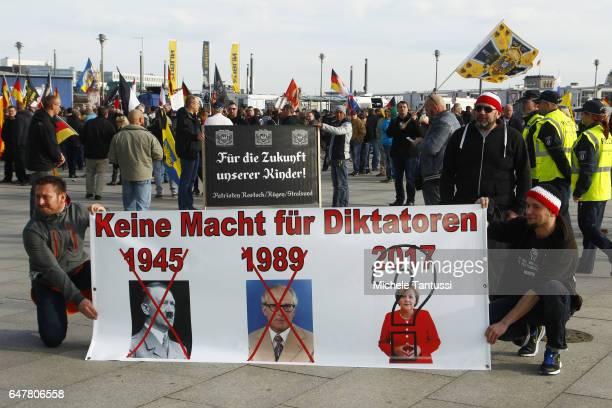 Protesters hold Germany Flag and Placard with right wing slogans against the Government and the Muslim religion at a Merkel muss weg gathering of...