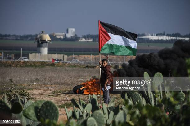 Protesters hold Palestinian flags as smoke rises during a protest against US President Donald Trumps announcement to recognize Jerusalem as the...