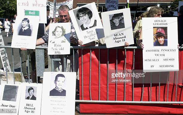 Protesters hold photos of alleged victims of sexual abuse outside the Cathedral of the Holy Cross during the installment of Sean Patrick O'Malley as...