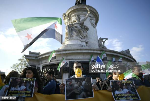 Protesters hold pictures and Syria's former independence flags during a demonstration to protest against chemical attacks in Syria on April 6 2017 on...