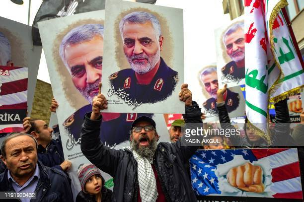 TOPSHOT Protesters hold pictures of Iranian commander Qasem Soleimani during a demonstration outside the US consulate in Istanbul on January 5 two...