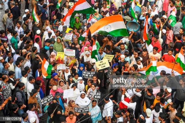 Protesters hold placards and national flags as they take part in a demonstration against India's new citizenship law in Kolkata on January 21 2020