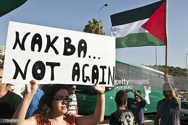 Protesters hold placards and Palestinian flags during a demonstration against Israeli government's plans to relocate Bedouins in the Negev desert in...