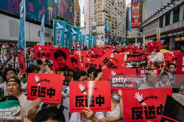 Protesters hold placards and shout slogans during a rally against a controversial extradition law proposal on June 9 2019 in Hong Kong Organizers say...