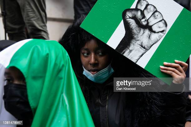 Protesters hold placards and signs calling for the end of police killings of the public in Nigeria, during a demonstration on October 21, 2020 in...