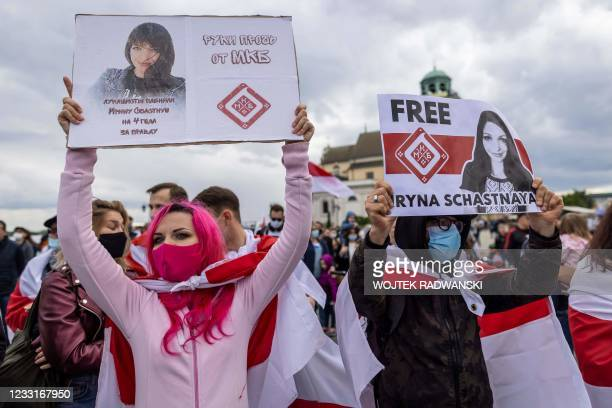 Protesters hold placards and traditional Belarusian flags, symbol of the opposition, as Belarusians living in Poland and Poles take part in a...