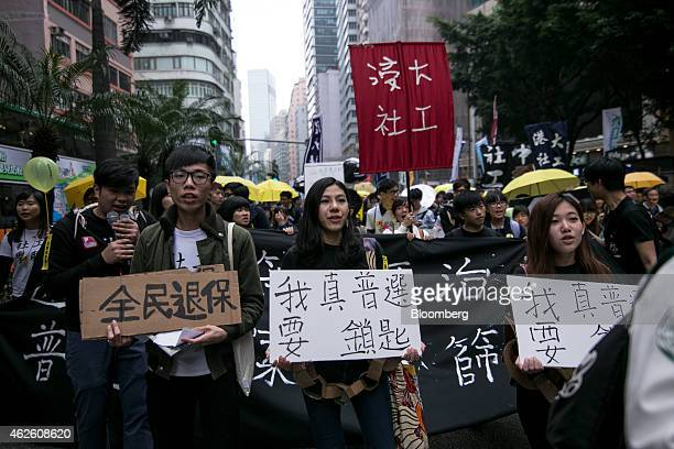 Protesters hold placards and yellow umbrellas as they march during a prodemocracy rally in Hong Kong China on Sunday Feb 1 2015 This is the first...