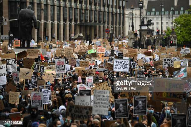 Protesters hold placards as they attend a demonstration in Parliament Square in central London on June 6 to show solidarity with the Black Lives...